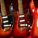 A row of electric Guitar on display with red velvet backrground,